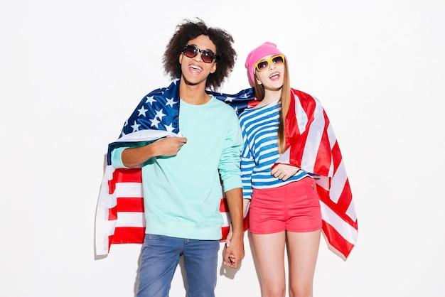Insouciant et amoureux. funky jeune couple couvrant de drapeau américain et souriant en se tenant debout sur fond blanc