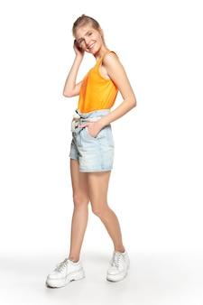 Insouciant. belle jeune fille en tenue élégante isolée sur fond de studio blanc. style de magazine, mode, concept de beauté. pose à la mode. copyspace pour l'annonce.