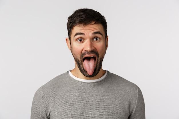 Insouciant drôle et ludique, gars maladroit avec barbe, porter un pull gris, montrant la langue