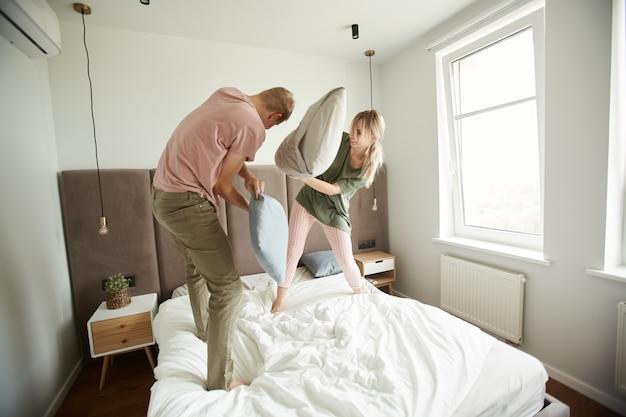 Insouciant jeune couple amoureux avec des oreillers s'amusant