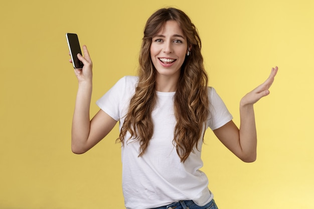 Insouciante belle fille aux cheveux bouclés sociable s'amusant avec des écouteurs sans fil dansant joyeusement en écoutant de la musique en mouvement chanson rythmique tenir un smartphone levant les mains caméra souriante amusée