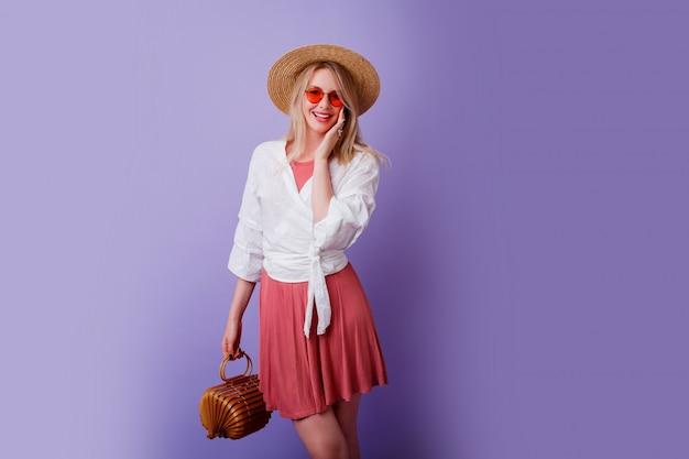Insouciante femme brune en robe rose à la mode et chapeau de paille tenant un sac en bambou sur violet.