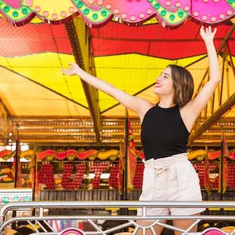 Insouciante jeune femme dansant au parc d'attractions