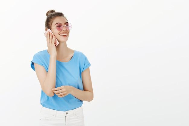 Insouciante jeune femme élégante à lunettes de soleil prenant le téléphone mobile et souriant