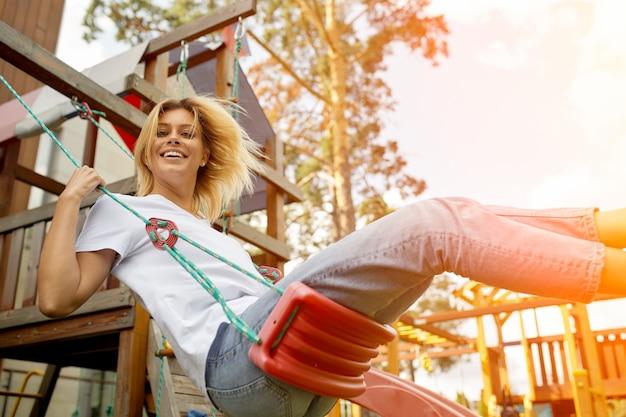 Insouciante jeune femme jouant sur une balançoire en corde se penchant sur le côté en riant de la caméra