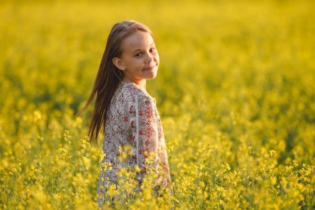 Insouciante jeune fille aime le coucher de soleil dans un champ