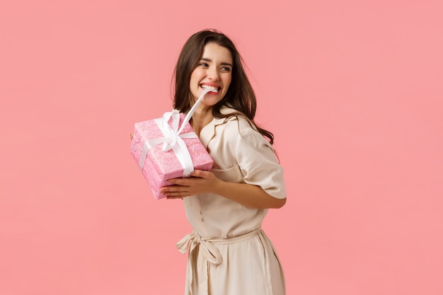 Insouciante jeune fille heureuse et optimiste faisant la fête, ayant un jour d'anniversaire incroyable, mordant le nœud sur un cadeau mignon
