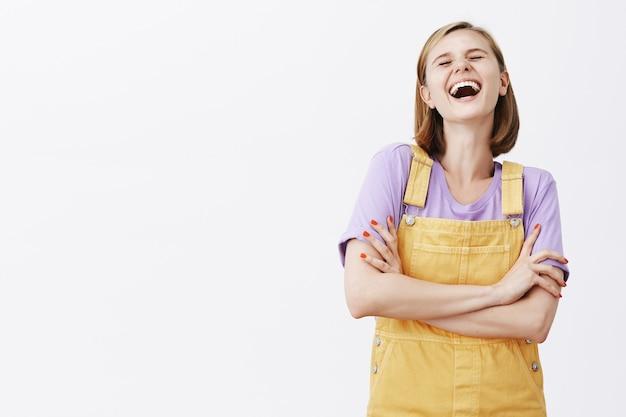 Insouciante jolie fille riante s'amusant, à la recherche de plaisir sur un mur blanc