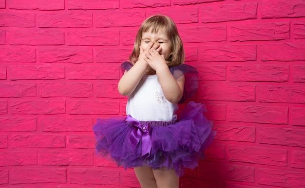 Insouciante mignonne petite fille en jupe tutu gloussant couvrant sa bouche avec sa main sur fond rose.