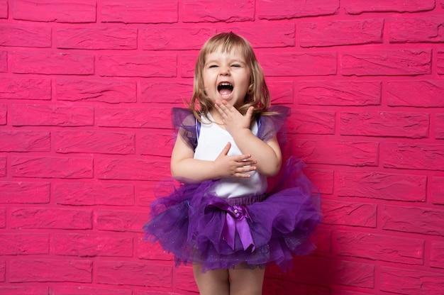 Insouciante mignonne petite fille en jupe tutu gloussant couvrant sa bouche avec sa main rose