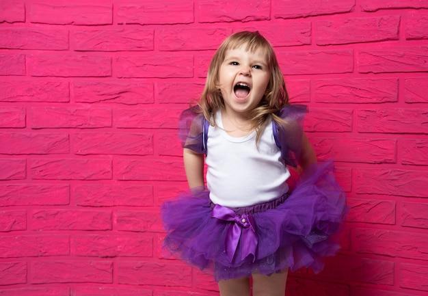 Insouciante mignonne petite fille en jupe tutu riant aux éclats de rire sur fond rose.
