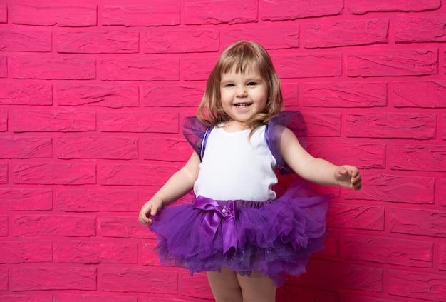 Insouciante mignonne petite fille en jupe tutu riant aux éclats de rire sur rose