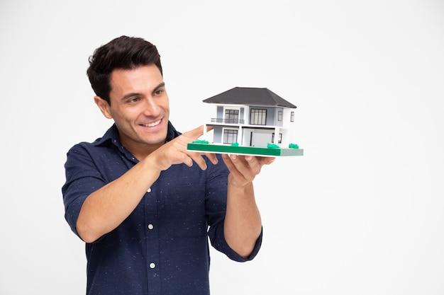 Inspecteur beau jeune homme caucasien tenant une maison unique.