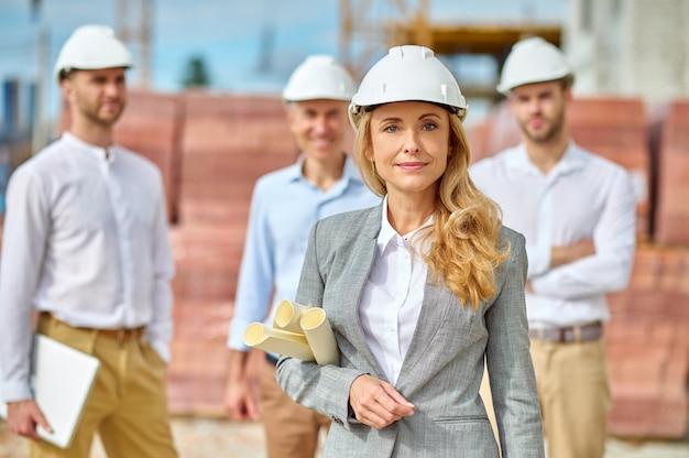 Inspecteur blond serein confiant avec des plans de construction debout à l'extérieur
