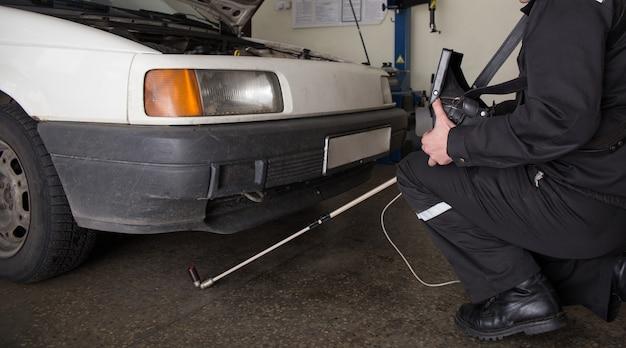 L'inspecteur du service des frontières recherche la contrebande dans la voiture avec la caméra au poste de contrôle frontalier international bruzgi