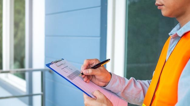 Les inspecteurs vérifient la structure de la nouvelle propriété et la notent dans le presse-papiers pour inspecter et réparer la maison avant de vendre aux clients.