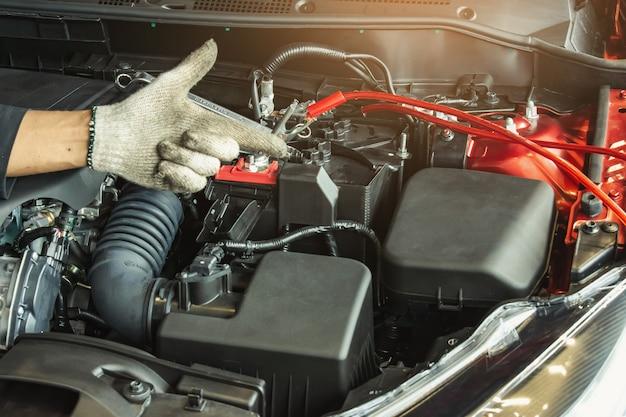 Cette inspection de carrière homme asiatique service de voiture charge voiture de batterie sur