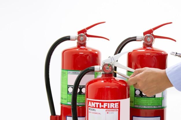 L'inspection de contrôle technique de protection contre les incendies services le réservoir d'extincteurs rouge.