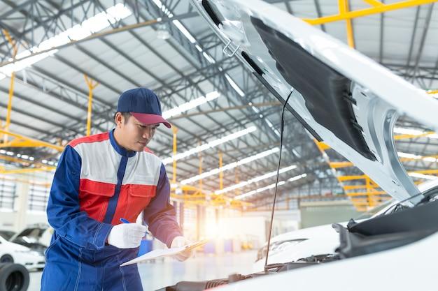 Inspection détaillée du véhicule par un mécanicien automobile asiatique.