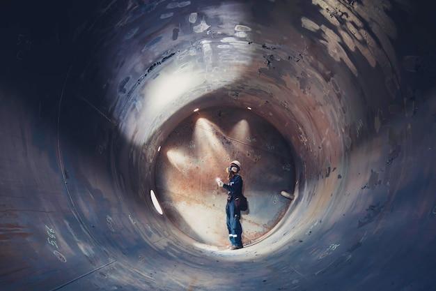 L'inspection des hommes travaillant soude sous terre du tunnel d'équipement de réservoir en utilisant la lampe de poche sur le côté confiné.