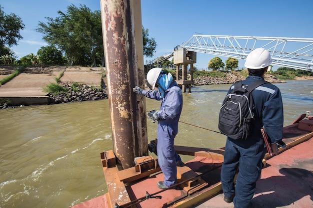 L'inspection des travailleurs masculins et la mesure de l'épaisseur du pipeline de pétrole et de gaz à la jetée