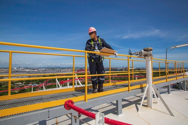 L'inspection visuelle des travailleurs du réservoir de stockage du toit de la ville d'arrière-plan d'huile et le ciel bleu.