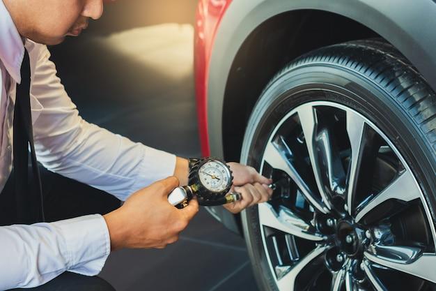 Inspection de voiture pour homme asiatique mesurer la quantité gonflé voiture en caoutchouc.