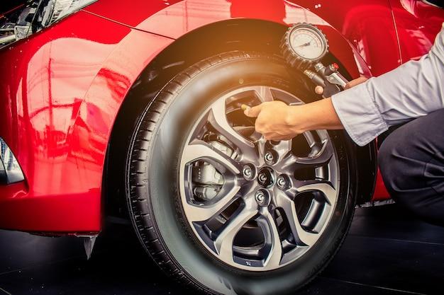 Inspection de voiture pour homme asiatique mesurer la quantité pneus en caoutchouc gonflés