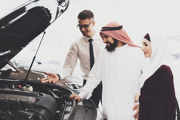 Inspection de la voiture sous le capot de la famille qatari la famille achète une voiture.