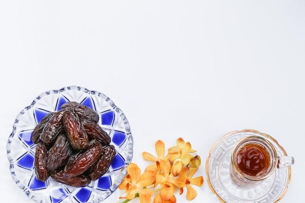 Inspiration du ramadan montrant des palmiers dattiers dans une assiette à motif islamique avec des fleurs d'orchidées et une tasse de thé