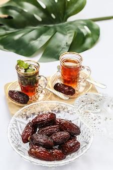 Inspiration du ramadan montrant des palmiers dattiers dans un bol en cristal avec des tasses de thé
