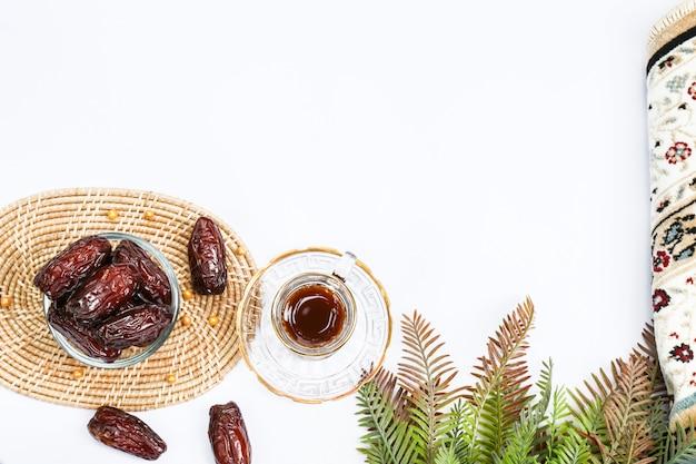 Inspiration du ramadan montrant des palmiers dattiers dans un bol avec du thé et un tapis de prière sur un fond blanc