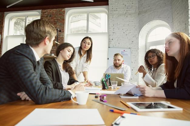 Inspiration. groupe de jeunes professionnels ayant une réunion. un groupe diversifié de collègues discute de nouvelles décisions, plans, résultats, stratégie. créativité, lieu de travail, affaires, finance, travail d'équipe.