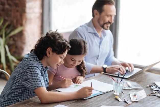 Inspiré de l'adorable frère et de sa charmante sœur assis à la table et peignant une image ensemble pendant que leur père travaille sur l'ordinateur portable