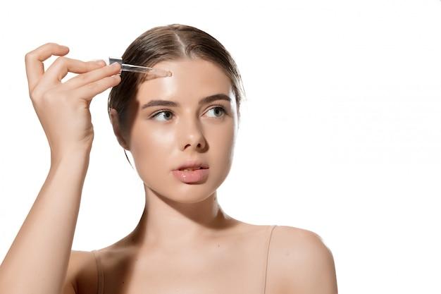 Inspiré. gros plan de la belle jeune femme avec des feuilles vertes sur son visage sur blanc. cosmétique et maquillage, soin naturel et éco, soin de la peau