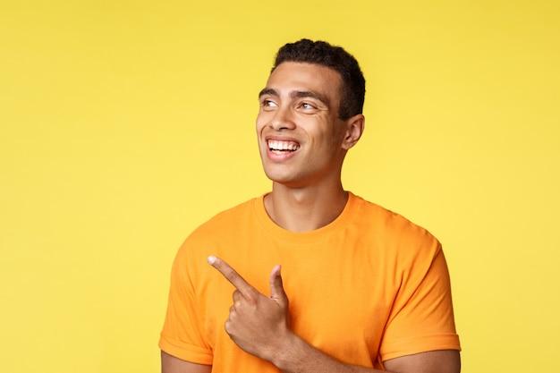 Inspiré, jeune étudiant athlétique chanceux en t-shirt, regardez intéressé et pointez vers la gauche