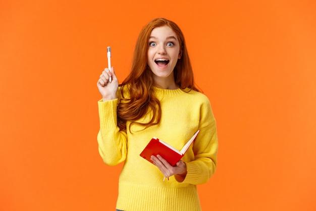 Inspirée et rêveuse, une étudiante rousse intelligente a une excellente idée pour son livre, écris dans un cahier