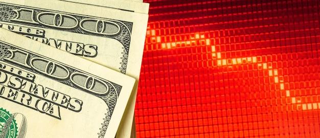 Instabilité dans le concept d'économie, récession et fond de crise mondiale avec des billets en dollars sur les graphiques des graphiques boursiers rouges, photo de bannière