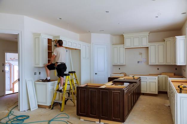 Installation d'armoires de cuisine.