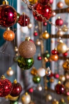 Installation d'art d'arbre de noël faite avec des guirlandes lumineuses et des boules de noël suspendues à des fils