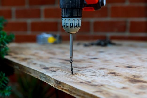 Installation de bois vis de torsion travailleur dans la planche de bois.