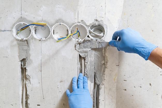Installation cachée de fils électriques pour prises sur un mur en béton