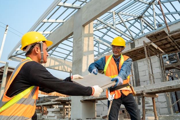 Installation de carreaux de toit en céramique par un ouvrier couvreur, concept de bâtiment résidentiel en construction.