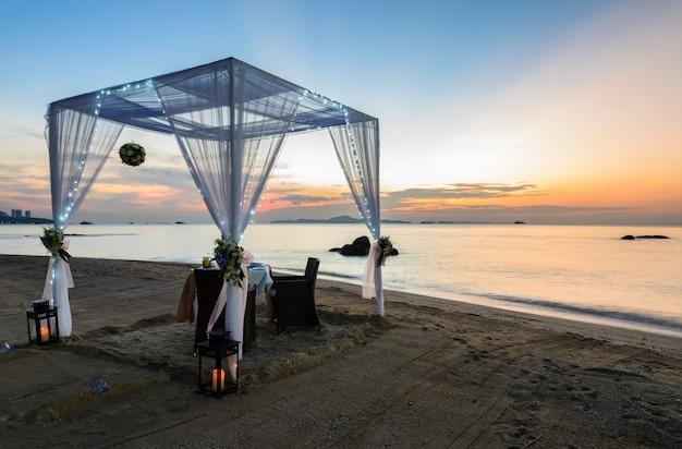 Installation d'un dîner romantique sur la plage au coucher du soleil