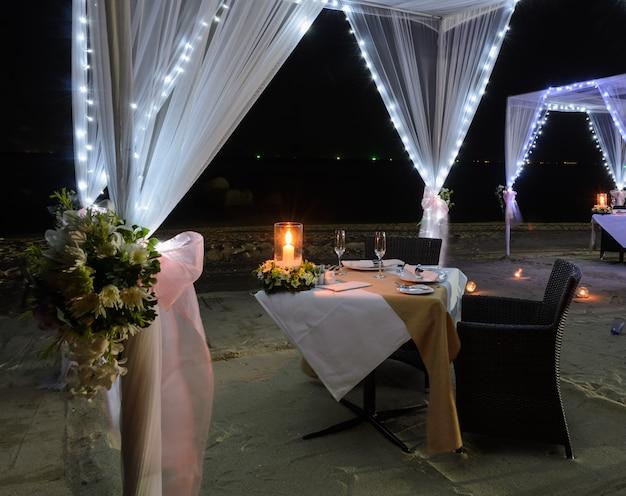 Installation d'un dîner romantique sur la plage la nuit