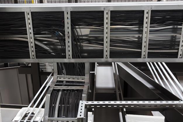 Installation d'échelles à câbles par ouverture du mur avec joint coupe-feu et plaque de recouvrement sur bâtiment industriel.