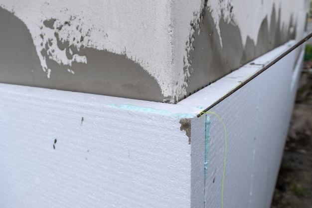 Installation de feuilles d'isolation en polystyrène sur le mur de façade de maison pour la protection thermique.