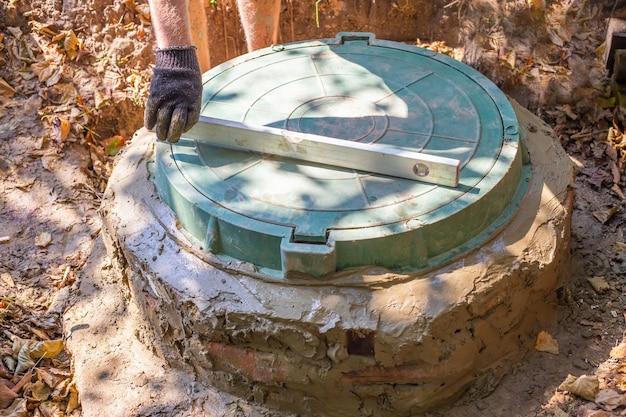 Installation d'une fosse septique avec un puits en anneaux de béton. nivellement du couvercle de la trappe.