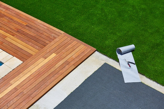 Installation de gazon artificiel dans le jardin sur le pont avec des outils
