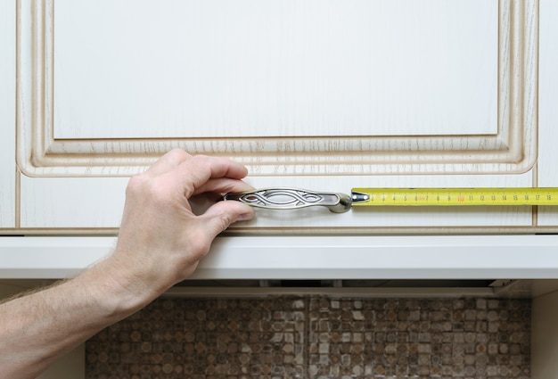 Installation de meubles de cuisine mesurant la distance où fixer l'armoire de poignée de porte